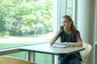 携帯電話で話す窓際の女子学生