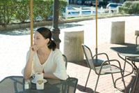 カフェのテラス席に座る女性