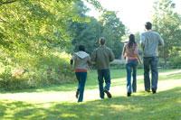 公園を歩くカップル2組の後ろ姿
