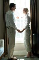 窓際で手をとり合うシニアカップル
