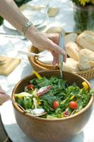 サラダをまぜるシニア女性の手元