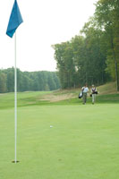 ゴルフ場を歩くシニアカップル