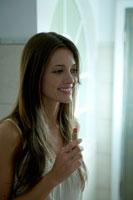 バスルームで口紅をつける女性