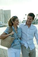 海沿いを笑顔で歩くカップル 24025000694| 写真素材・ストックフォト・画像・イラスト素材|アマナイメージズ
