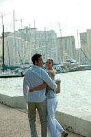 海沿いを笑顔で歩くカップル
