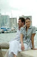 海沿いに座ってリラックスするカップル