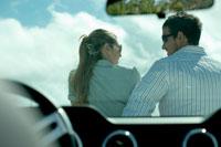 車の前で会話をするカップル