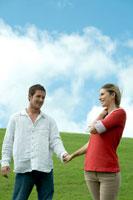 芝生の上で手を繋いで散歩するカップル