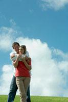 芝生の上で女性を抱きしめる男性