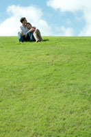 芝生の上に座って女性を抱き寄せる男性