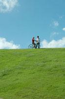 公園で自転車に乗る女性と側を歩く男性 24025000759| 写真素材・ストックフォト・画像・イラスト素材|アマナイメージズ