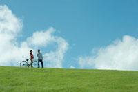 公園で自転車に乗る女性と側を歩く男性