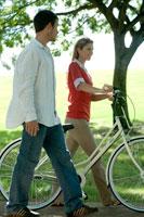 公園で自転車を引く女性と側を歩く男性