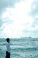 海沿いで遠くの船を眺める男性