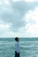 海沿いで遠くを眺める男性