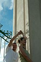 フェンスの影の中でダンスをするカップル