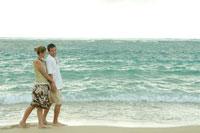 海岸で手を繋いで散歩するカップル