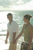 海岸で手を繋いで散歩するカップル 24025000812| 写真素材・ストックフォト・画像・イラスト素材|アマナイメージズ