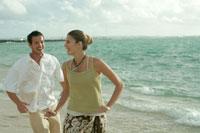海岸で追いかけっこをするカップル
