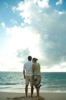 海岸で夕日を眺めるカップル 24025000818| 写真素材・ストックフォト・画像・イラスト素材|アマナイメージズ