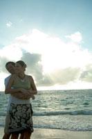 夕日の中海岸で寄りそうカップル