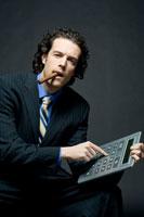葉巻をくわえ電卓で計算をするビジネスマン