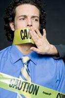 注意と書かれたテープで口を塞がれるビジネスマン