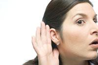 手を耳にあてて話を聞こうとする女性