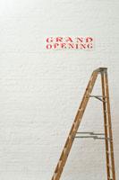 壁に貼られた開店ポスターと梯子 24025000896| 写真素材・ストックフォト・画像・イラスト素材|アマナイメージズ