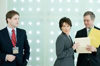 周囲を気にしながら書類を確認するビジネスマン