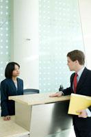 オフィスの受付で立ち話をするビジネスマン