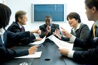 会議室で議論するスーツ姿の男女