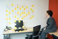 壁一面に貼られたメモを見つめるビジネスウーマン
