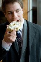 ベーグルを食べるビジネスマン
