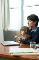オフィスでパソコンを見つめる母親と娘