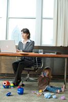 オフィスで働く女性と床で遊ぶ娘