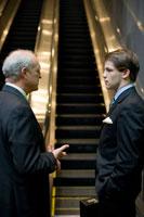 エスカレーターの前で立ち話をするビジネスマン