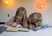 ベッドで日記を書く女性2人