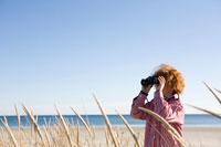 海岸で双眼鏡で遠くを眺める男の子