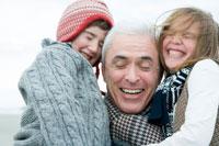 海岸で孫を抱くシニア男性