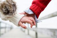 ビーチデッキで手を繋ぐ男の子と女の子の手元