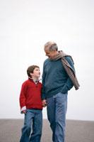 街中を散歩するシニア男性と孫息子