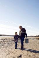 海岸で潮干狩りをするシニア男性と男の子