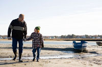 海岸で手を繋いで散歩するシニア男性と男の子
