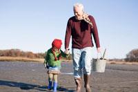 海岸で手を繋いで散歩するシニア男性と女の子