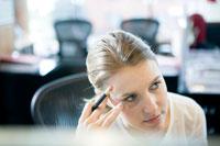 オフィスのデスクで頭を抱える女性