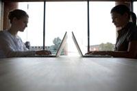 向き合ってパソコンで仕事をする女性たち