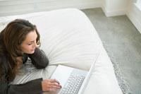ベッドの上でパソコンをする女性