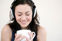ソファーでコーヒーを飲みながら音楽を聴く女性
