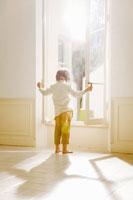 窓を開ける少年の後ろ姿